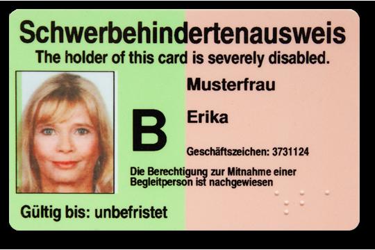 Schwerbehindertenausweis liegt auf einem Tisch zusammen mit Kleingeld, Kopfhörern und anderen Ausweisen.